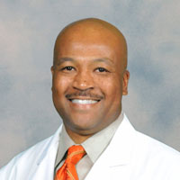 Image of Dr. Stanley Lewis in a white lab coat with an orange tie